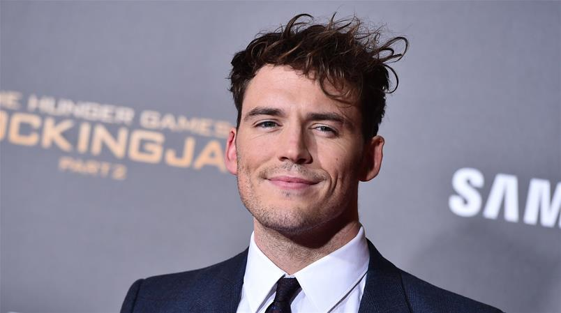 """Sam Claflin, wearing a Mockingjay pin with the French tricolor, arrives at the Los Angeles premiere of """"The Hunger Games: Mockingjay - Part 2"""" at the Microsoft Theater on Monday, Nov. 16, 2015. (Photo by Jordan Strauss/Invision/AP)"""