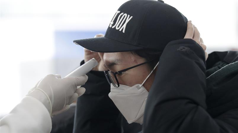 A voter wearing face mask, has his temperature checked upon his arrival to cast a ballot during an early voting for the April 15 general elections at a local polling station in Seoul, South Korea, Friday, April 10, 2020. The early voting for the April 15 general elections start for two-days on April 10-11 at 3,508 polling stations across the country. (AP Photo/Lee Jin-man)